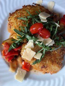 hausgemachte Rösti mit Ratatoille-Gemüse  Rucola-Salat und Parmesan-Spänen garniert